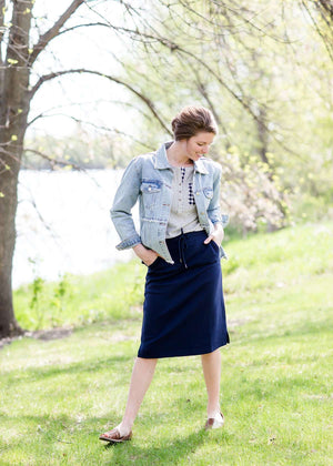 Woman wearing a below the knee sweatshirt material skirt that has pockets and drawstrings. This skirt is black, navy and gray.