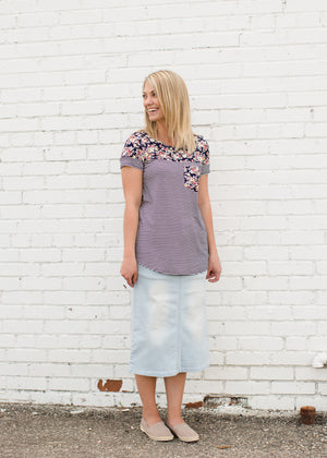 Young lady wearing a light denim below the knee jean skirt.