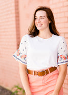 White top with multi color floral embroidered knit sleeves