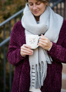 Woman wearing a gray fringe scarf that is super cozy and knit.