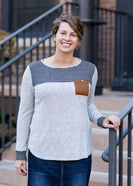 Woman wearing a gray color block stripe top with a brown, suede pocket with a button feature.