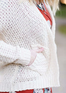 Young woman wearing a ivory chunky knit acrylic and wool sweater. This sweater has front pockets and features an open front.