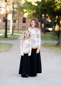 Woman and daughter wearing a blush floral modest sweatshirt with thumbholes that is lined with a mustard trim