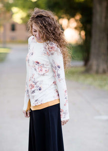 Woman wearing a blush floral modest sweatshirt with thumbholes that is lined with a mustard trim