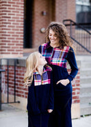 This half zip pullover features a front pouch pocket and a beautiful color block print of fuchsia, teal and mustard!  This young girl is also matching her mother in a mommy and me style.