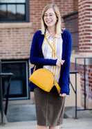 Young woman wearing a modest navy open front cardigan with front pockets and buttons over a mustard striped blouse