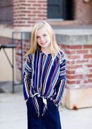 Young girl wearing a multi colored striped dolman top with a front tie. Colors in this top are navy, yellow, red, purple, green and white!