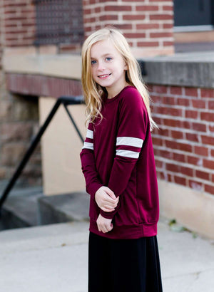 Young girl wearing a modest burgandy long sleeve raglan style sweatshirt! It has contrasting stripes on the arms and is super comfortable!