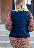 Woman wearing a cold weather, quilted puffer vest. This vest comes in mauve, black, navy and wine. It features pockets and a front zip.