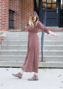 Woman on staircase wearing a rust colored, geometric print, smock maxi dress.