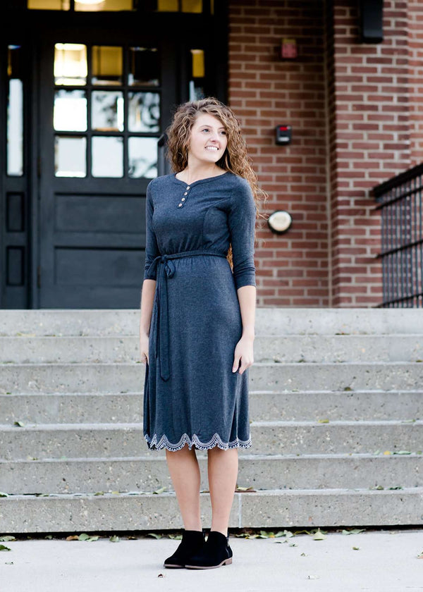 Inherit Co.  | Inherit Originals | Tessa Midi Dress | Woman wearing a modest, below the knee charcoal gray, lined midi dress. This dress has faux buttons and a removable belt. It is a 3/4 dress and paired with a pair of black sole society shoes.
