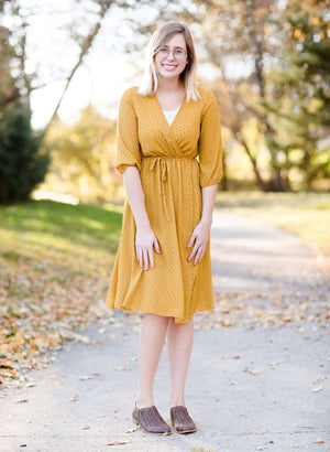 Young woman wearing a modest golden printed midi dress that has a faux wrap and is nursing friendly