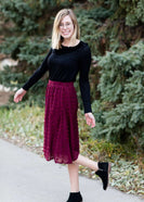Young woman wearing a a burgandy modest midi skirt that has swiss dot details all over it. This skirt is also fully lined and has an elastic waist.