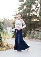 Woman wearing a long denim skirt with no slit that has buttons up the front and is a flare style, a-line skirt.