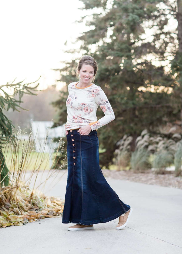 Woman wearing a long denim skirt without a slit that has buttons up the front and is a flare, a-line style.