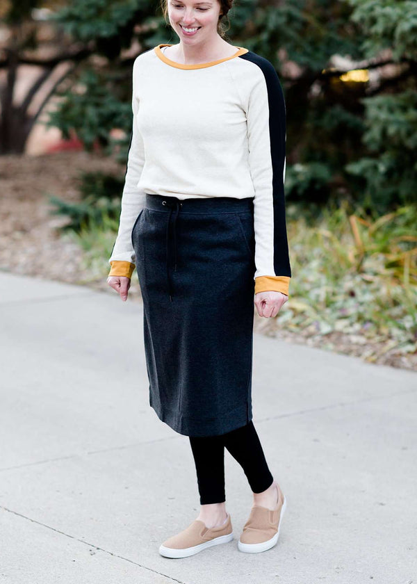 Inherit Co.  | Inherit Originals | Serena Midi Skirt | Woman wearing a below the knee sweatshirt material skirt that has pockets and drawstrings. This skirt is black, navy and gray.