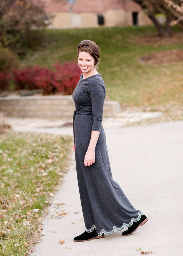 Inherit Co.  | Women's Modest Dresses | Tessa Maxi Dress | Woman wearing a charcoal gray maxi dress that has lace scalloping on the bottom, is 3/4 sleeve and is lined. It also has faux wood buttons on the bodice and a removable belt.