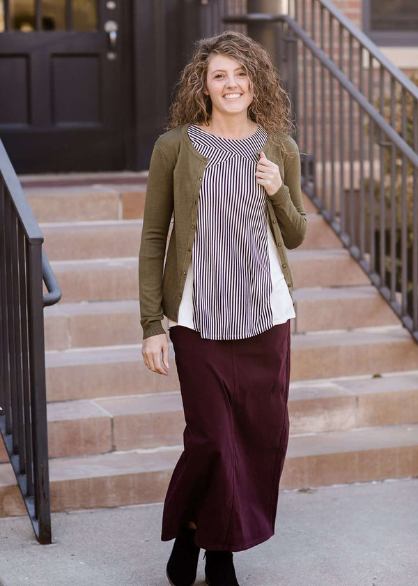 Inherit Co.  | Essential Crewneck Cardi | Woman wearing a modest and classic pink, burgandy, emerald and olive colored button up crewneck cardigan with a midi skirt