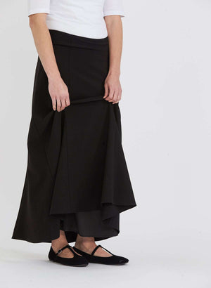 Woman wearing a black, dressy church skirt with panels and a side zipper. This long skirt has panels and a flowy bottom as well.