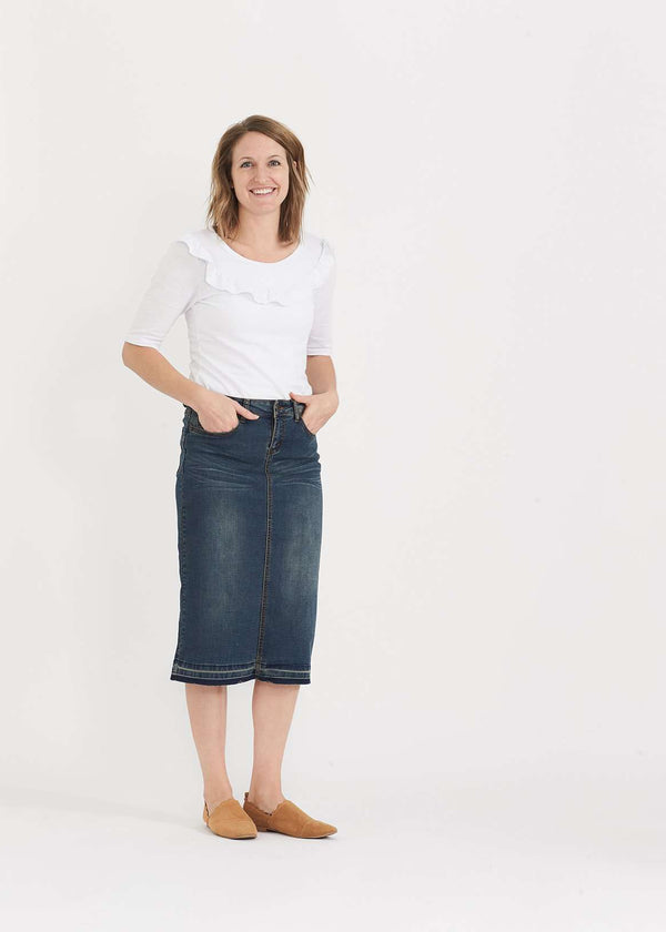 5a046a8885 Woman wearing a denim below the knee jean skirt. This skirt has a raw edge