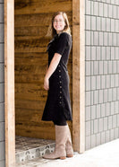 Woman wearing a ribbed black midi dress with brown buttons cascading on the left, bottom side of the dress. This short sleeve modest dress is paired with black leggings and tall suede riding boots.