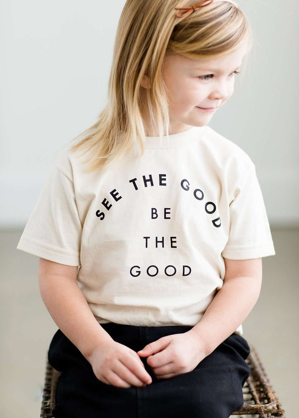 "Toddler girl wearing an ivory graphic tee that says ""see the good, be the good"" in black ink. She is also wearing a modest below the knee black skirt and tan colored booties."