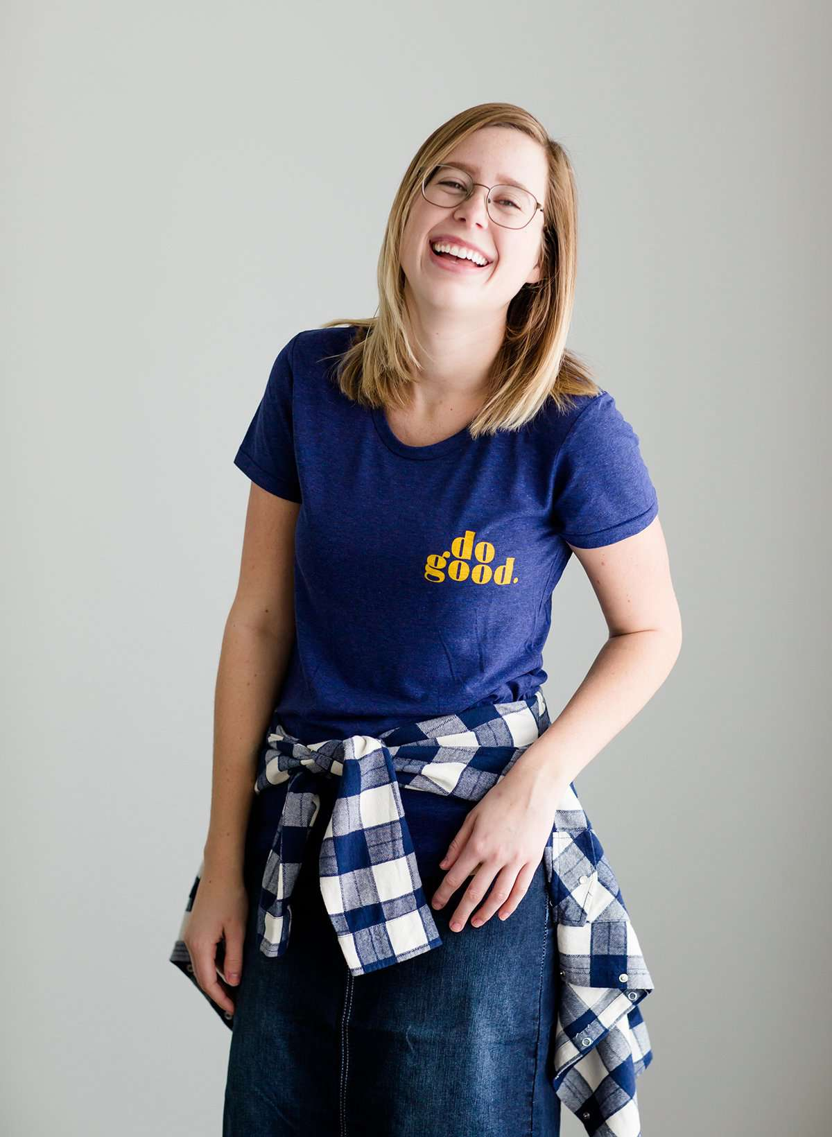 "Young woman wearing a blue graphic tee with yellow words that says ""Do Good."" It is also paired with a below the knee denim skirt and a plaid button up top."