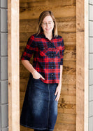 Woman wearing a cozy, checkered plaid top. This button up plaid shirt features roll tab sleeves and is black, navy and red. It is also paired with a below the knee jean skirt.