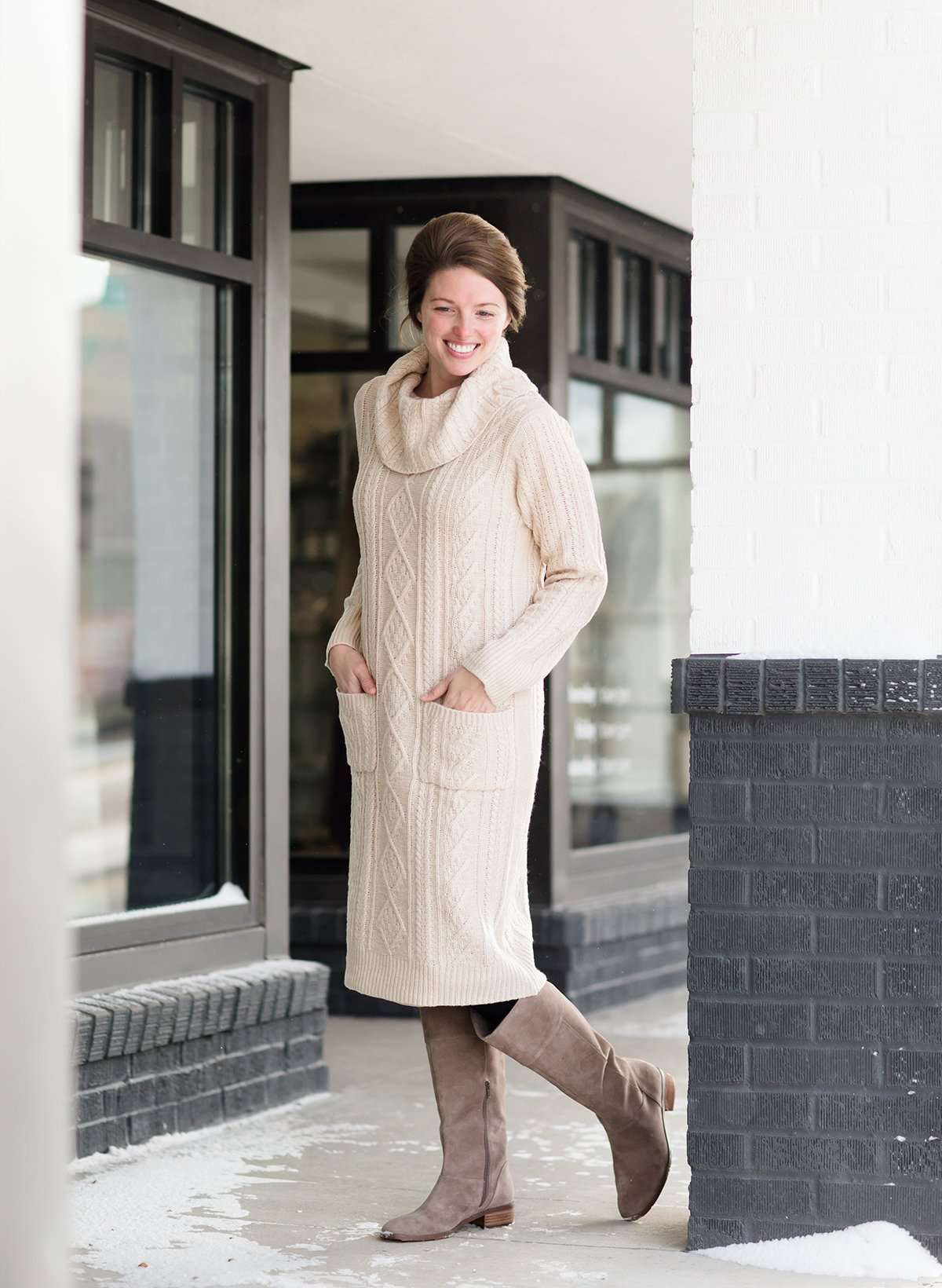 Woman wearing a cableknit, cowlneck sweater dress in taupe or burgandy. This cozy dress is below the knees and paired with tall, suede riding boots.