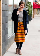 Woman wearing a modest mustard and burgandy striped midi skirt. This skirt has a fabric belt that is removable and is also mommy and me styled. This skirt is paired with tights and boots.