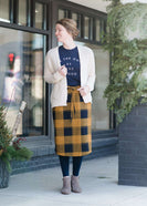 Woman wearing a modest plaid sweater style midi skirt. This skirt has an elastic waist and a tie front. It is paired with tights and short ankle boots.