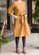 Woman wearing a modest mustard and stripe color midi dress. This dress has oversized pockets a belted front and is paired with tights and brown booties.