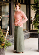 Woman wearing an olive, long modest cotton skirt. This skirt has no slit and is paired with a mauve sweater.