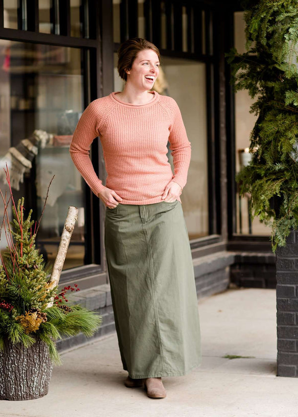 Inherit Co.  | Nottingham Cotton Twill Skirt | Woman wearing an olive, long modest cotton skirt. This skirt has no slit and is paired with a mauve sweater.