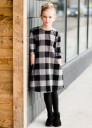 Young girl wearing a black and white buffalo check midi dress. This dress has 3/4 sleeves and front pockets. It is paired with black leggings and black booties.
