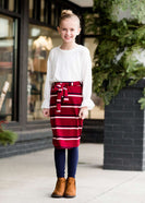 Young girl wearing a burgandy and mustard striped midi skirt with removable belt. This is also a mommy and me skirt. It is paired with a white ruffle top, leggings and brown boots.