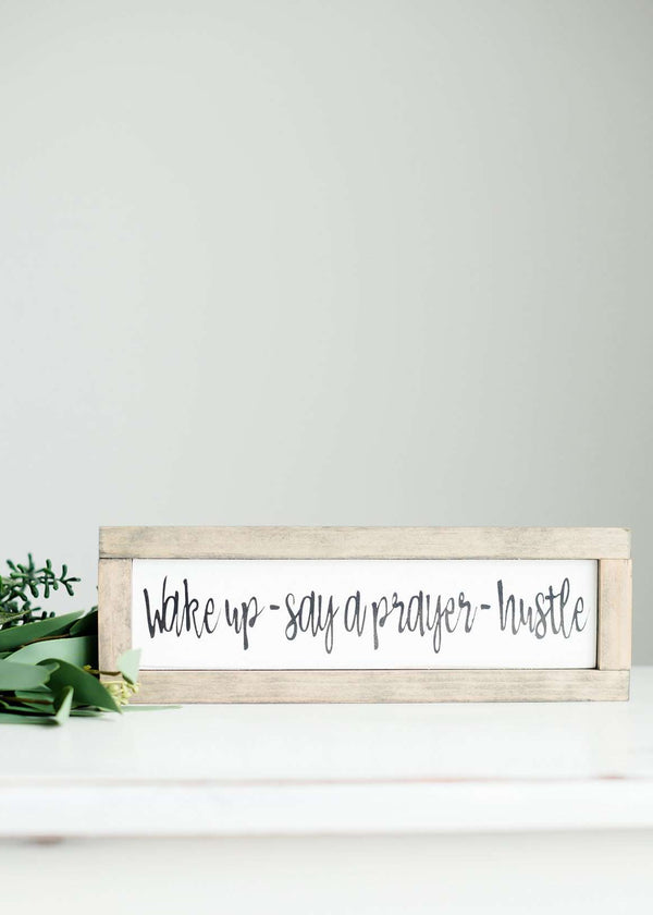 "Wood Frame Signboard with the words, "" wake up, say a prayer + hustle"" written in a fun font."