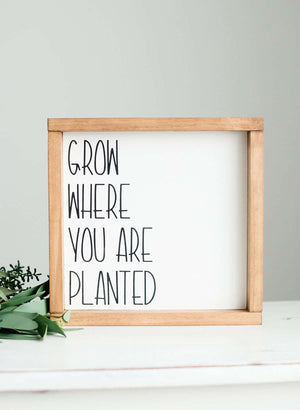 "Woodframe Signboard that has script writing that says "" Grow where you are planted""."