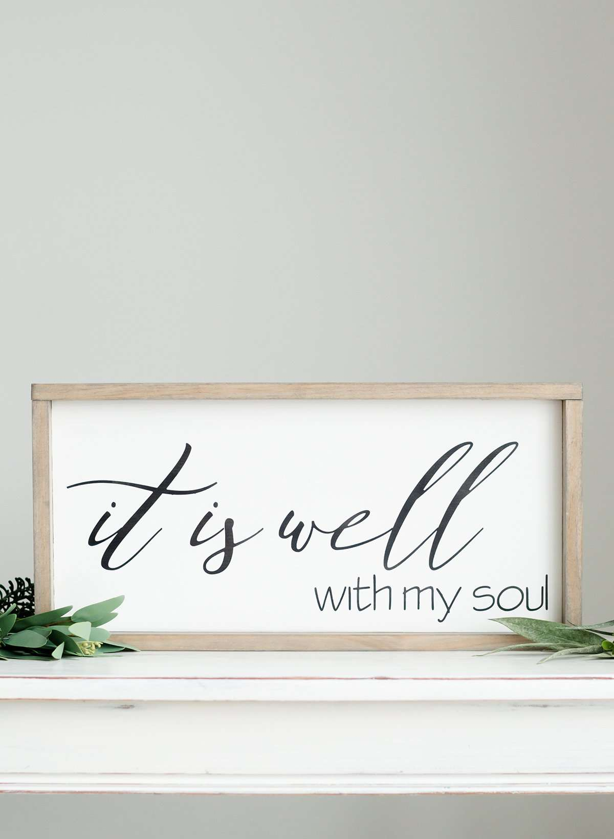 "Wood Frame Signboard with the words"" It is well with my soul"" printed on it in black script font."