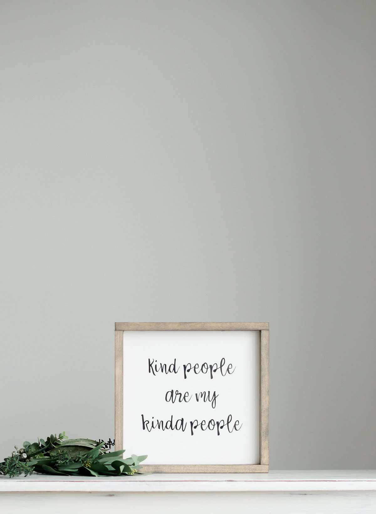 "Wood Frame Signboard with the words, "" kind people are my kinda people"" written in a playful script font."
