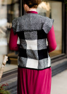 Woman wearing a sailor color, open front, black and white checker drape vest