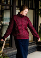 Woman wearing a modest cable knit, Burgundy sweater with a below the knee skirt. She is standing outside of Inherit Clothing Company.