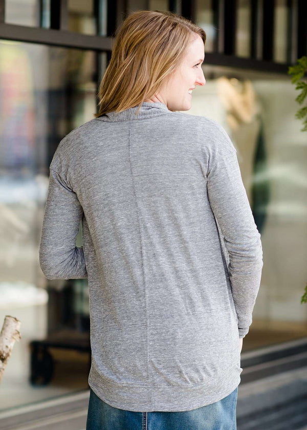 Inherit Co.  | Pomme de Terre Open Cardigan - FINAL SALE | Woman standing in front of Inherit Clothing Company wearing a Minnesota screen printed, gray, open cardigan. The Minnesota screen print is pink.