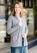 Woman standing in front of Inherit Clothing Company wearing a Minnesota screen printed, gray, open cardigan. The Minnesota screen print is pink.