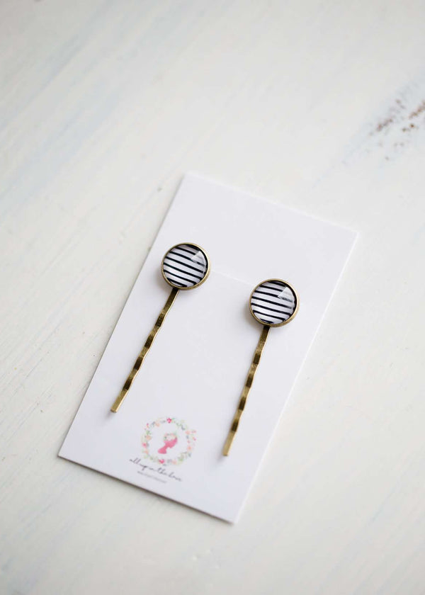We love these classic, Striped Bobby Pins! These make a fun addition to your hair for small bursts of style. You will find these make a great gift too!
