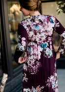 Woman wearing a modest, plum and navy maxi dress that has a elegant, floral print.