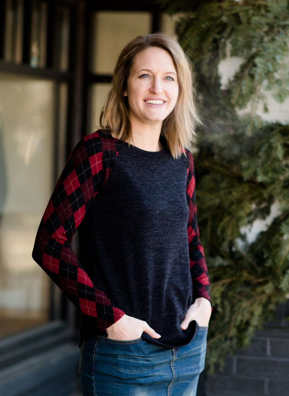 Woman wearing a dark charcoal raglan style top with diamond, argyle checks that are black and red. She is standing outside of Inherit Clothing Company.