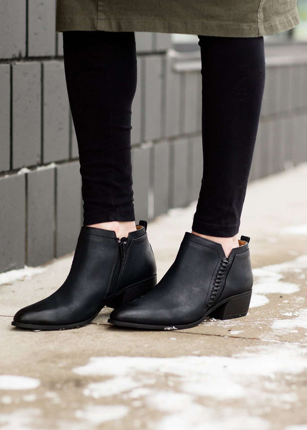 Stacked black ankle boots with a delicate side braid, made of man-made materials.