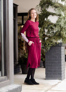 Woman wearing a burgandy and lace midi dress with black tights and sole society back boots. She is standing outside of Inherit Clothing Company.
