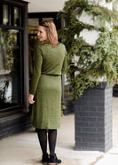 Woman wearing a olive colored hacci midi dress with a elastic waist and paired with black sole society boots
